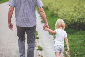 Father walking with daughter holding hands